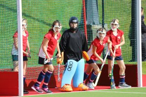 Girls with hockey sticks waiting in goal area on hockey pitch