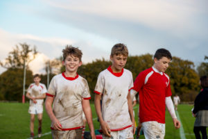 Three Prep School boys in rugby kit walking across a rugby field