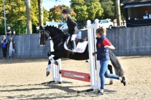 Young girl on horse jumping over a low jump with helping running alongside