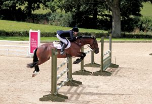 Girl on horse jumping over a jump at Hickstead Showground