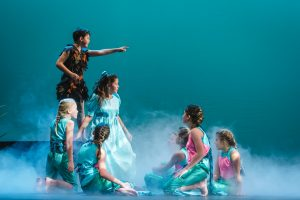 Children on stage surrounded by mist, acting in Peter Pan